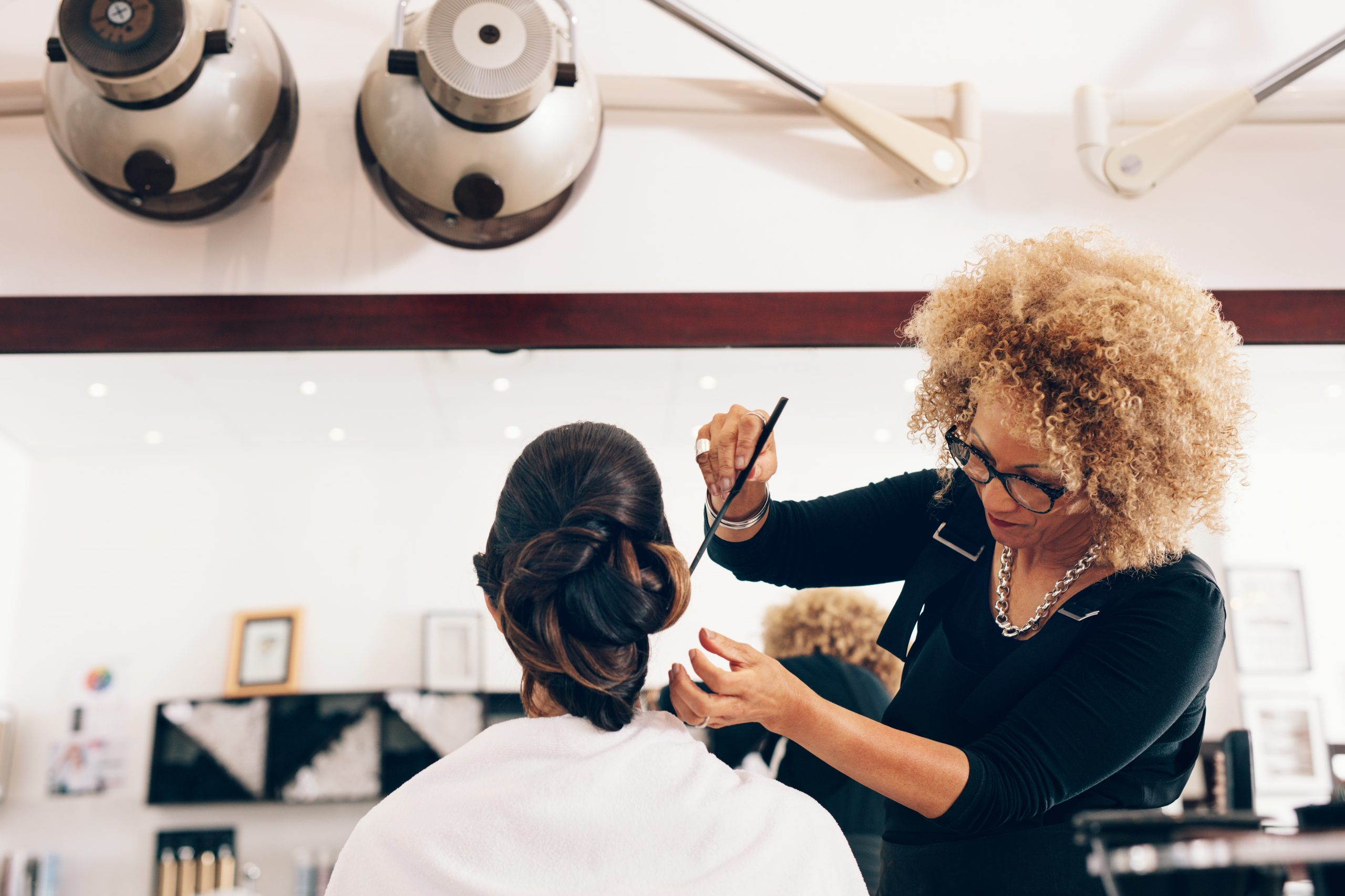 Un coiffeur professionnel coiffant les cheveux d'un client au salon. Coiffeuse styliste mettant les cheveux dans un design à la mode.