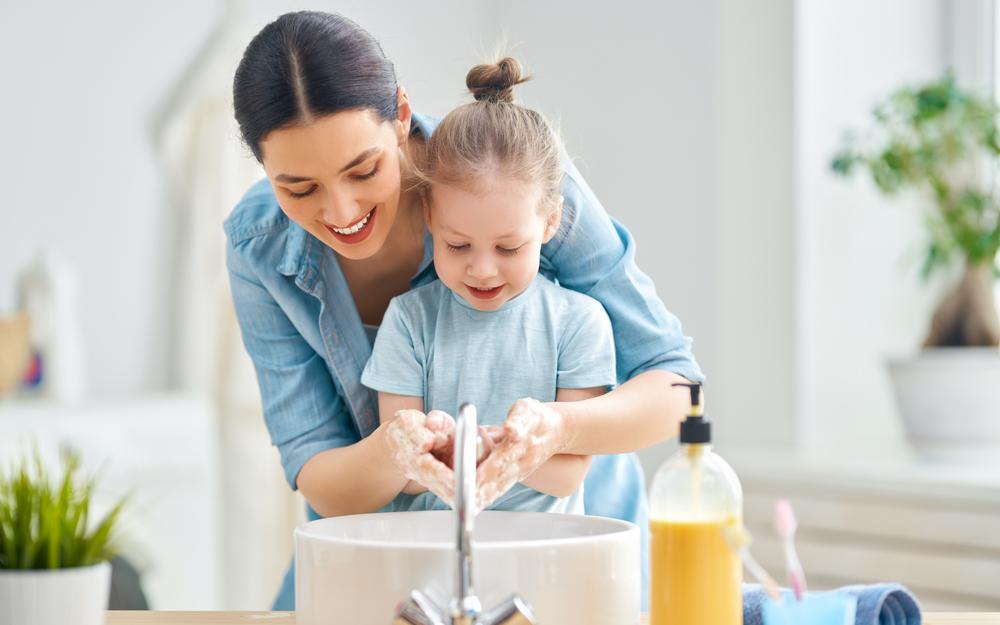 Un efant et un adulte qui se lavent les mains