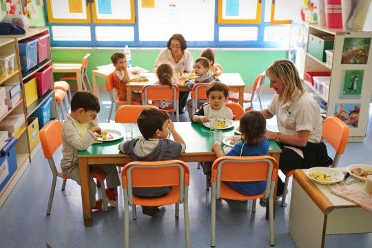 Une ATSEM supervisant le repas de jeunes enfants à l'école maternelle.