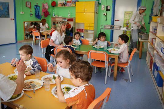 Une ATSEM en compagnie de tout-petits à l'école maternelle.