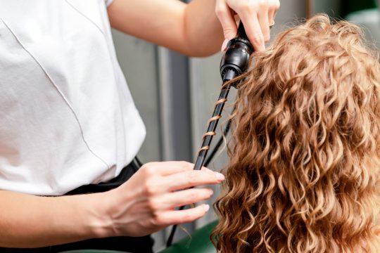 Le coiffeur tient les cheveux d'une femme en bouclant ses cheveux au fer à boucler dans un salon.