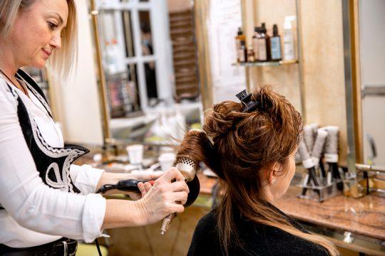 La coiffeuse utilise le sèche-cheveux Blow pour sécher les cheveux mouillés de la cliente. Coiffeur fabriquant une nouvelle coiffure au salon. Travailler dans le secteur de la beauté