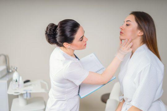 Cosmétologie professionnelle examinant la peau du visage d'une fille à la clinique de cosmétique esthétique