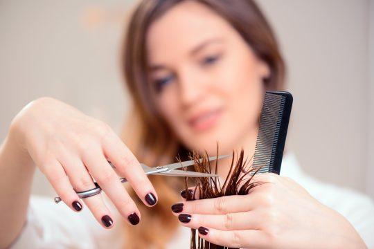 mage de mise au point sélective de la belle coiffeuse faisant une coiffure à son client tout en se tenant sur le fond d'un salon de coiffure professionnel