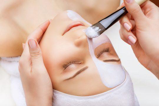 Application d'un masque facial à la femme sur fond blanc