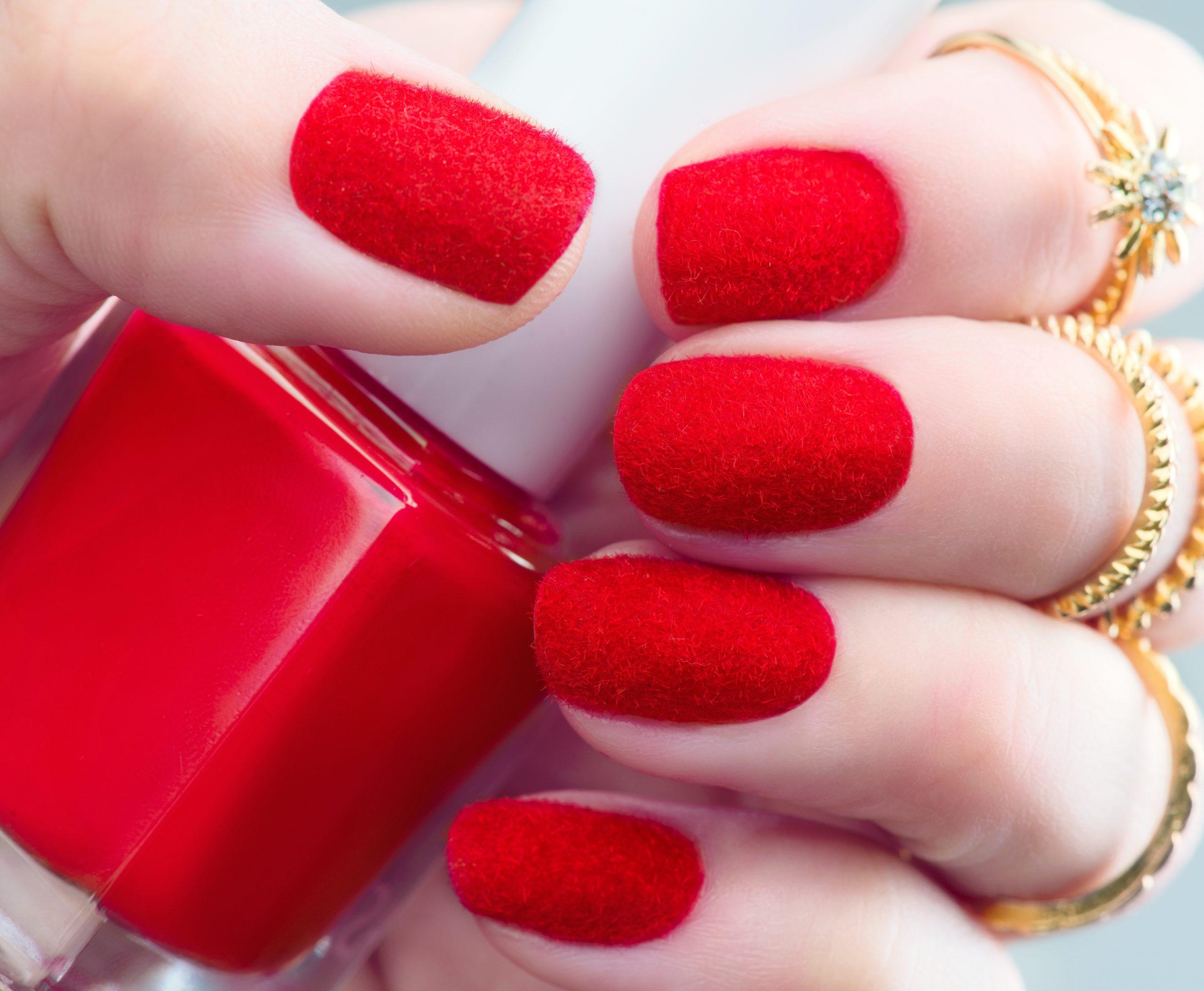 Ongles de velours. Mode création d'ongles rouges fluffy tendance en gros plan