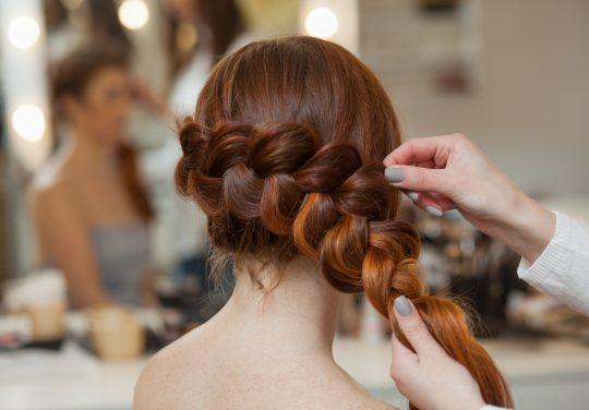 coiffeuse tisse une tresse française, en gros plan dans un salon de beauté