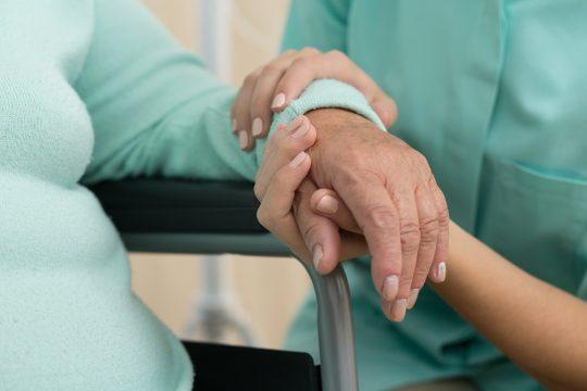 Photo d'une assistant médicale soutenant la vieille femme en fauteuil roulant